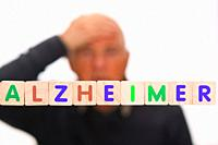 senior man suffering from Alzheimer disease and holding his head behind letters meaning Alzheimer concept
