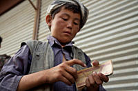 A young boy counts his earnings as porter, at the main market of Mazar_e_Sharif, in the northern province of Balkh An estimated 60,000 children have f...
