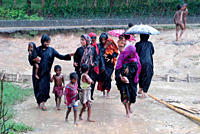 A group of women from the Kutupalong Rohingya Refugee Camp brave the rain on their way back from a child care centre after taking treatment for their ...