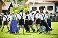 Couples wearing traditional costumes passing meadow, May Running, Antdorf, Upper Bavaria, Germany