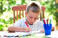 Cute little boy coloring outside