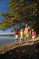 Family walking along the lake shore of Lake Saffelsee, Upper bavaria, Bavaria, Germany