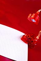 Red heart shaped lamp making light over a piece of paper
