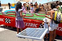 Children playing with solar powered Scalextric set at the Eolica festival of renewable energy on Tenerife, Canary Islands, Spain
