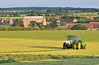 Tractor Baling forage hay, Binham priory and village in background, Norfolk, UK, June