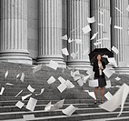 Mixed race businesswoman on steps with swirling papers