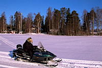 Woman driving snowmobile near Lulea, Lapland, Sweden, Scandinavia, Europe