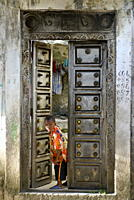 Young boy curiously looking through an old antique door, Moroni, Grand Comore, Comores, Indian Ocean, Africa
