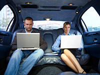Businesspeople with laptops in limousine