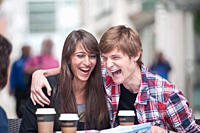 Couple seated at cafe table, laughing
