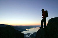 A walker above Windermere lake on Todd Crag at dawn lake district uk