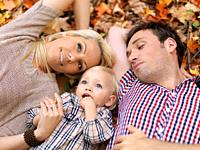 Happy smiling young parents and a two year old girl lying on colorful fallen tree leaves in autumn nature