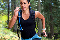 Hispanic woman with backpack running in forest