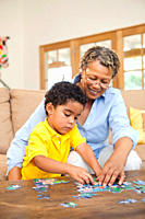 Grandmother and grandson putting puzzle together
