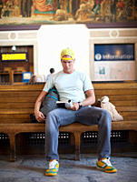 Caucasian man reading book in train station