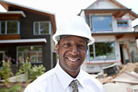 Smiling Black real estate agent in hard_hat near construction site