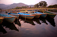 Row of colourful boats on Phewa Tal lake at dusk sunset, Pokhara, Rukum district, Nepal