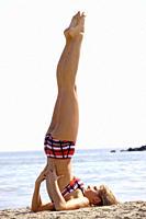 Woman does gymnastics on the beach