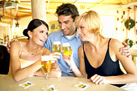 Man flirting with two women at a hotel bar