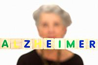 Alzheimer concept, senior woman sitting behind colored letters, spelling Halzheimer