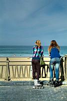 two girls on roller skates at the seaside  Zurriola beach  Donostia-San Sebastian  Spain