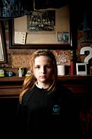 Interior, Sullen looking 12 year old girl, facing the camera, UK