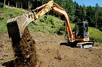 Tracked excavating machine emptying a bucket of soil, levelling ground, Wales