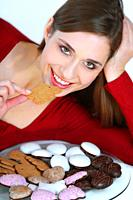 young brunette woman eating christmas cookies