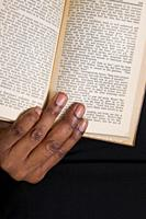 Close-up of a black woman's hand holding a book