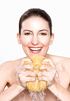 Woman holding sponge, smiling, portrait