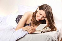 Woman lying on bed and reading book, smiling