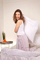 Woman on bed playing with pillow and shouting