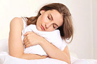 Woman holding pillow and sleeping, eyes closed