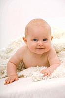 Baby boy 6_11 months lying on bed, smiling, portrait