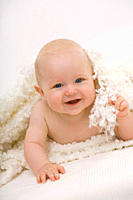 Baby boy 6-11 months lying on bed, smiling, portrait (thumbnail)