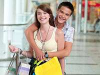 Smiling teenage couple shopping in mall