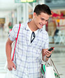 Teenage boy text messaging on cell phone in mall