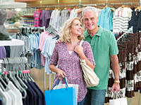 Smiling couple carrying shopping bags in clothing store