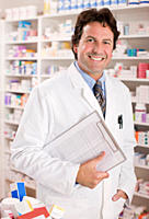 Smiling pharmacist holding clipboard in drug store