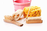 Sponges and brushes with basket on white background