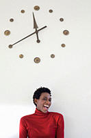 Germany, Leipzig, University student laughing with wall clock in background