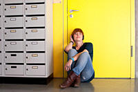 Germany, Leipzig, Young woman sitting and listening music in locker room