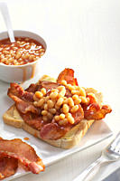 Bacon on toast with baked beans in bowl