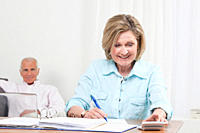 Woman doing paperwork with man sitting in background