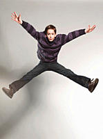 Boy 12_13 jumping against gray background