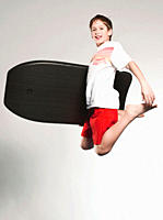 Boy 12_13 jumping with boogie board, smiling, portrait