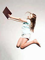 Girl 10-11 holding book and jumping, smiling (thumbnail)