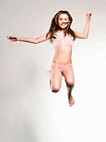 Girl 10-11 jumping and smiling, portrait (thumbnail)