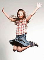 Girl 8_9 jumping with arms up, smiling