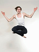 Man jumping with legs crossed and gesturing, portrait